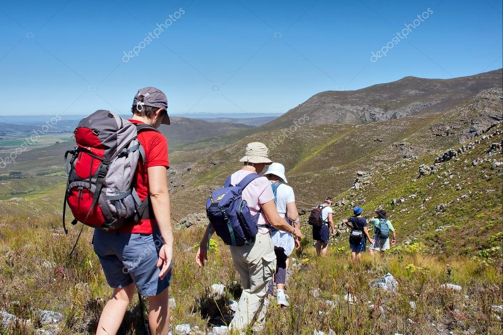 Group of female hikers walks downhill
