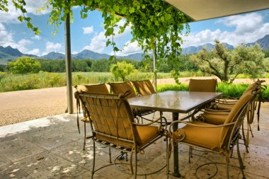Table in vine-covered pavillion next to magnificent mountains