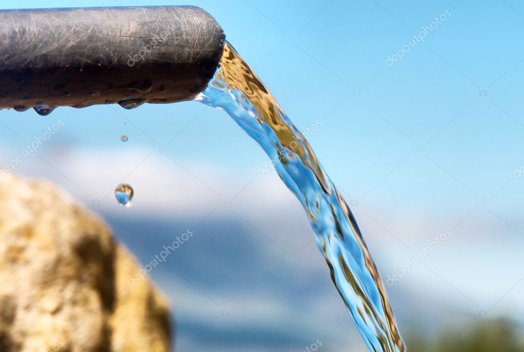 Water flowing from pipe against blurred mountains