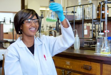 Happy African female researcher with glass equipment