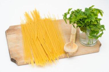 Spaghetti on a wood board with wood spoon