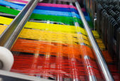 Textilipari gép, szivárvány színű szálak