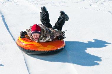 Happy boy sleding on a tube down a hill. stock vector