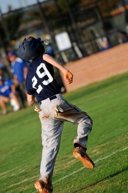 Teen baseball player running bases