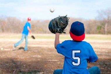 Two boys playing baseball at the park