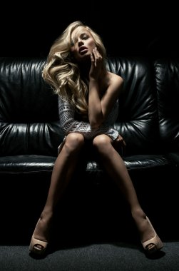 Beautiful blonde woman on black couch