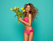 Fotografie Beautiful blonde woman in pink swimsuit with bouquet of yellow t