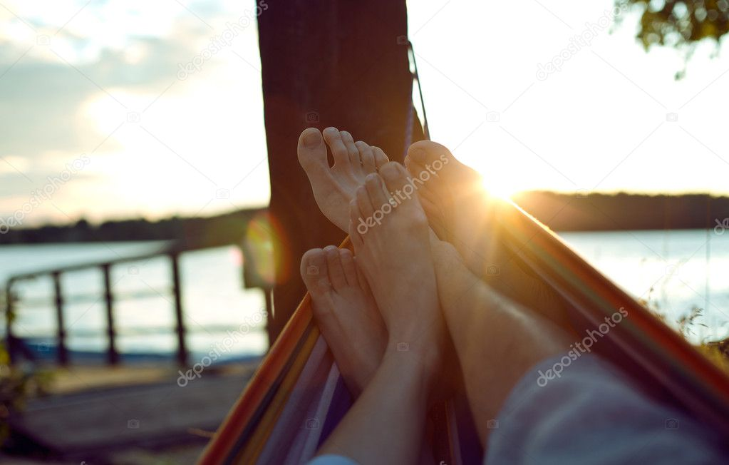 Vacation photo of couple feet relaxing on beach on hammock