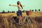 Fotografie freie Frau genießen Freiheit auf Fahrrad am Weizenfeld bei Sonnenuntergang