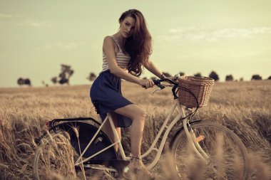 Attractive woman with bike in wheat field