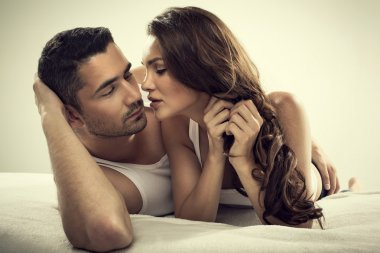 Handsome man and sexy woman in bed
