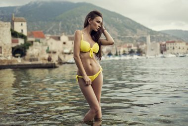 Fashion shoot of sexy woman wearing yellow swimsuit