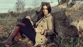 Fotografie junges Mädchen sitzen im Freien in Herbstlandschaft