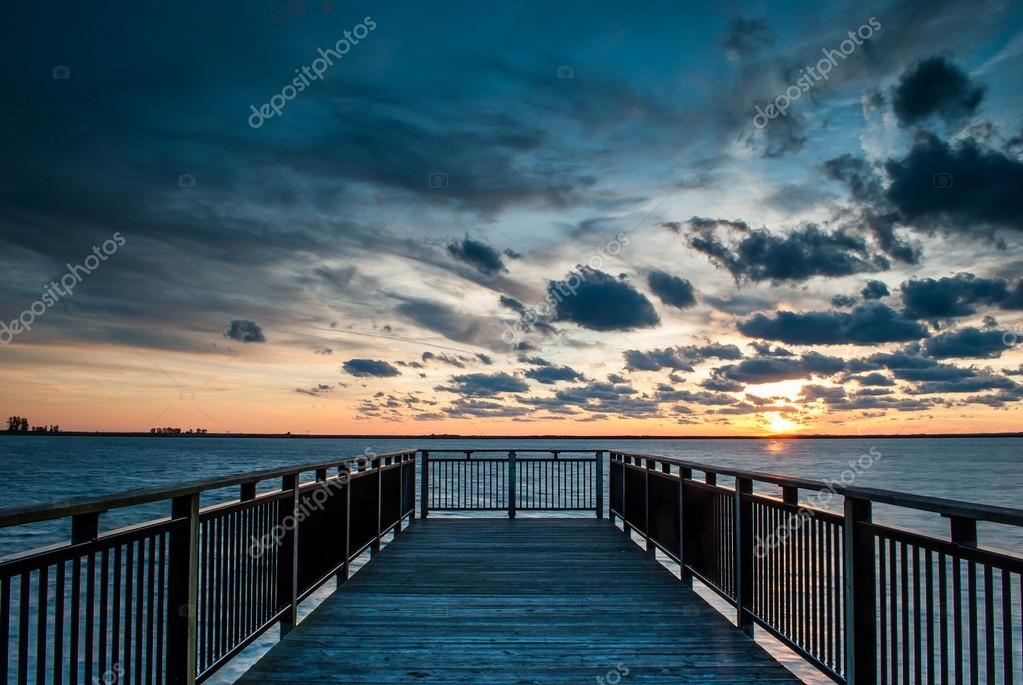 Backlit Pier at Sunset with Sun and Clouds
