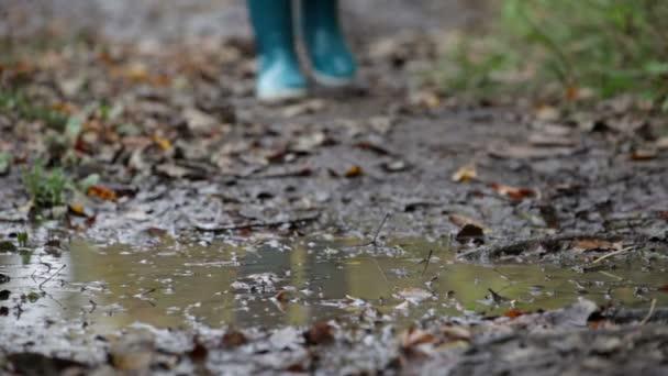 botas de lluvia caminando en un charco de lodo y tierra en ...