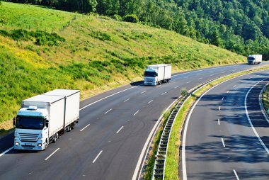 Highway with three oncoming white truck in a wooded landscape