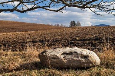 Big white stone next to the undulating plowed field in early spring