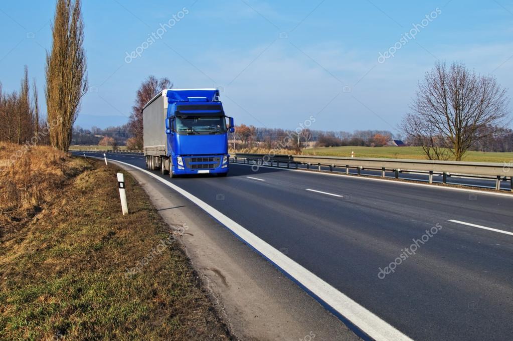 Rural landscape with an asphalt highway and blue truck