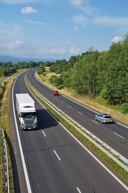 Highway passing through the countryside, truck and passenger cars