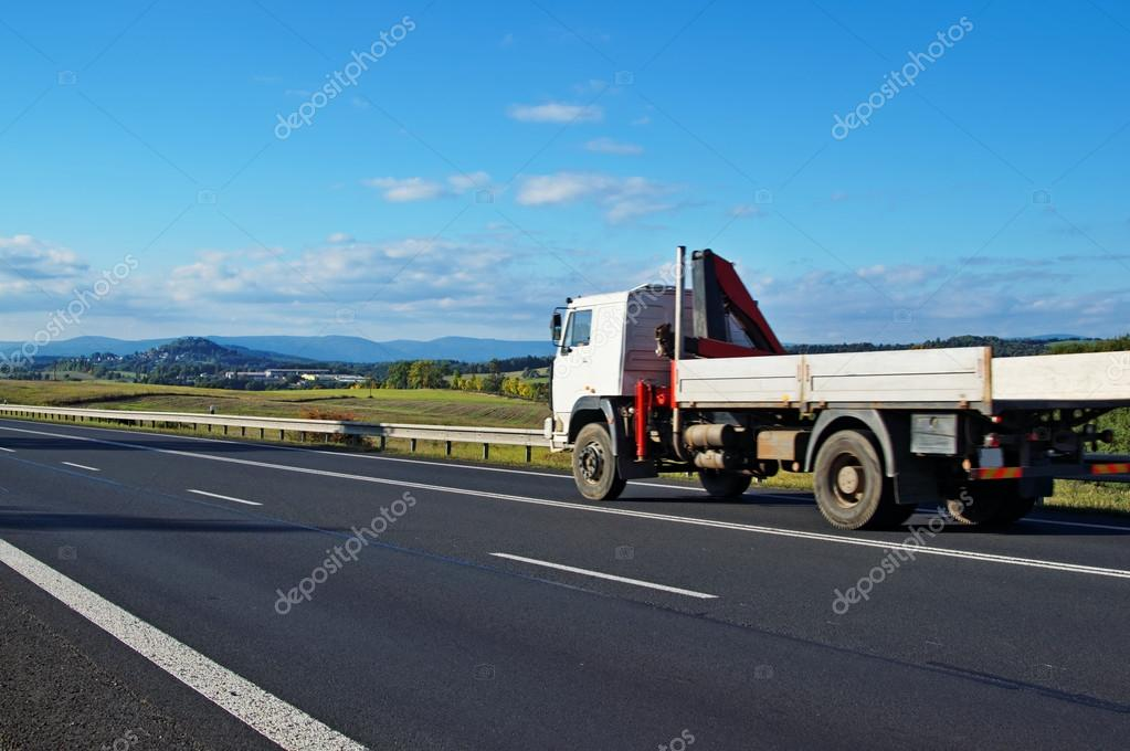 Rural landscape with road and moving truck