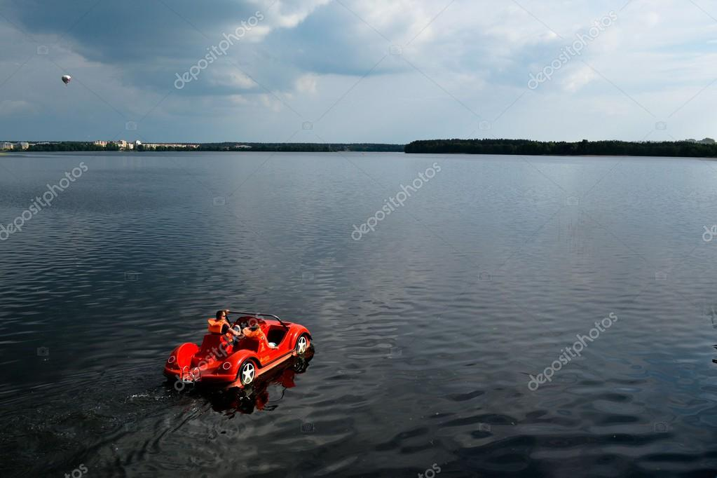 Red car - pedal boats floating on a calm lake