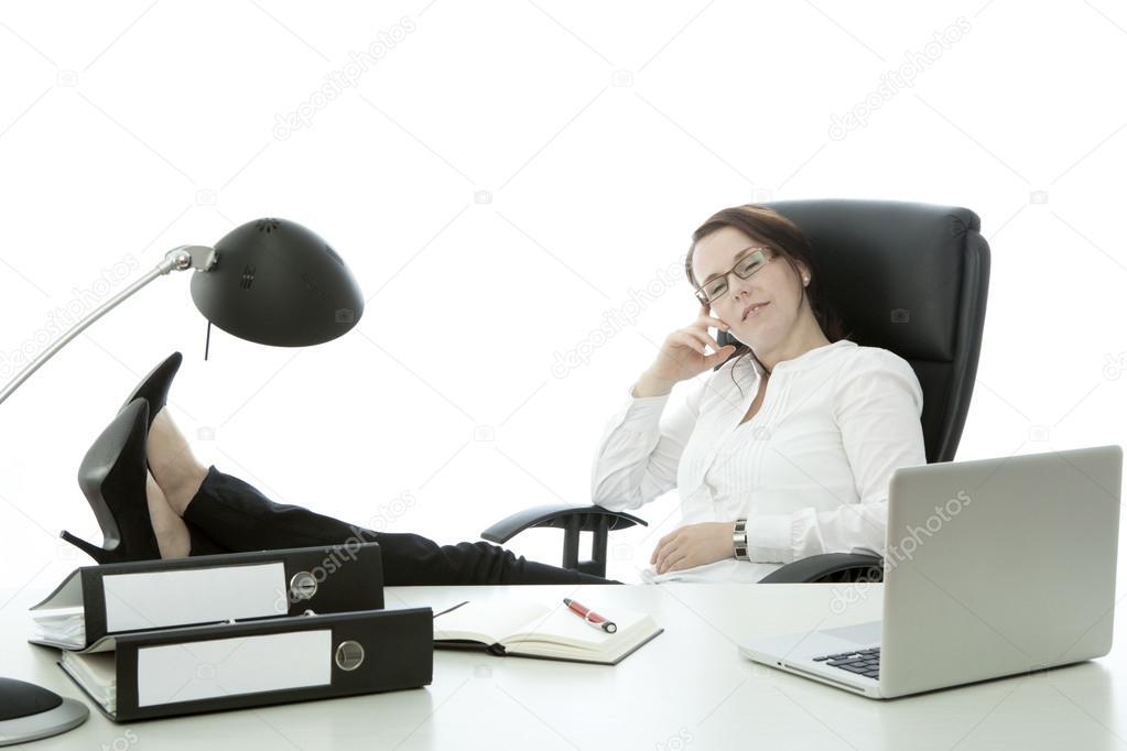 Jeune femme brune avec des lunettes se détendre avec pieds bureau