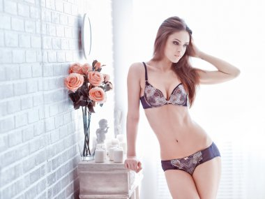 Sexy young woman inlingerie posing near decorate brick wall with flowers