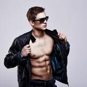 mladý pohledný macho muž v sluneční brýle s otevřenou koženou bundu