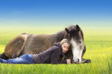 Girl and horse lying and sleep on field, sunny summer day,  against  blue sky,liberty,horsemanship