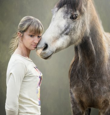 Gray brown horse cuddles with blonde woman