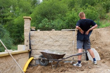 back pain, bricklayer builds a wall