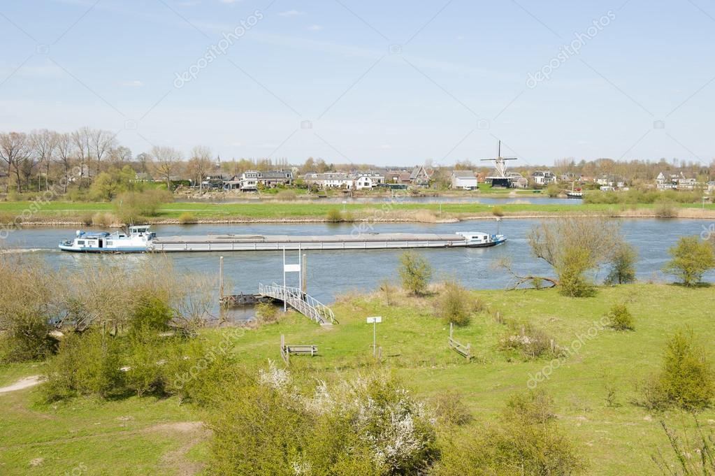 River cargo ship in rural landscape