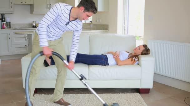 frau schlafen auf dem sofa w hrend der mann die hausarbeit stockvideo 23715665. Black Bedroom Furniture Sets. Home Design Ideas