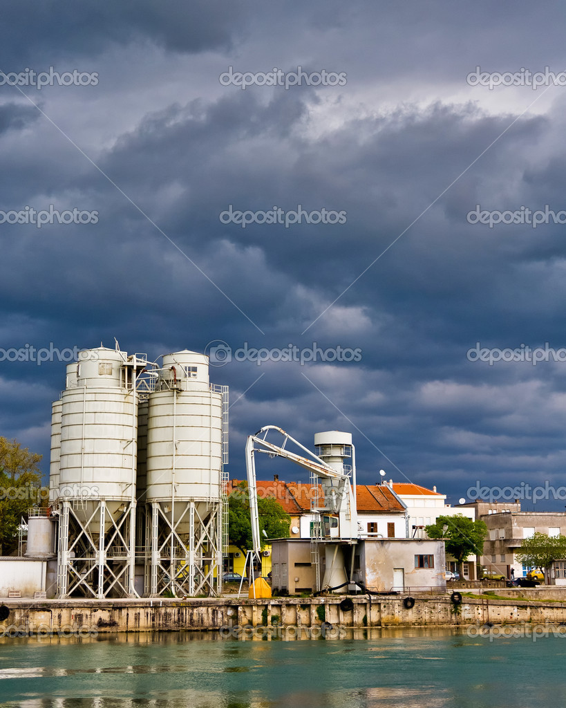 Silos for storage in the industrial river port with dramatic clouds above.