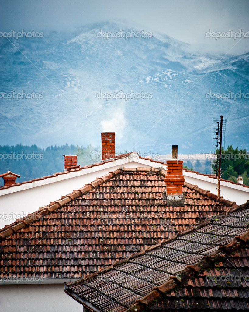 Rooftops with smoking chimneys in winter