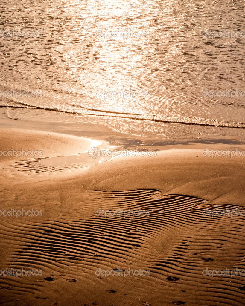 Warm sunset on textured sand beach