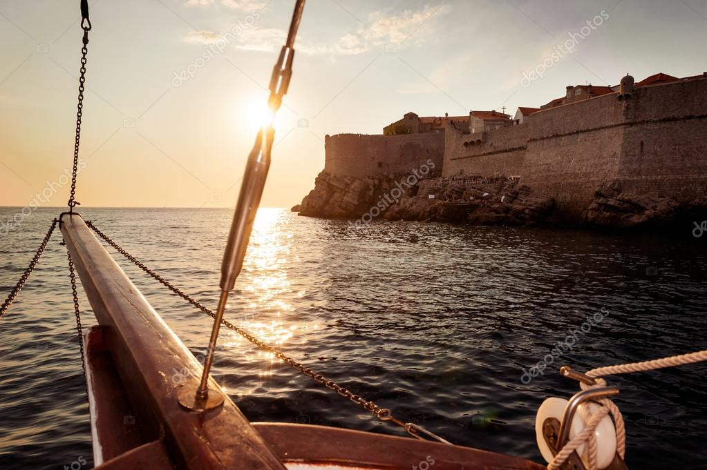 Old sailing ship sails into the sunset next to the city walls of