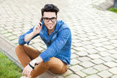 Fotografie handsome young man talking on a smartphone outdoors