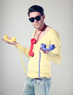 handsomen and funny guy with hipster glasses and colouful phones