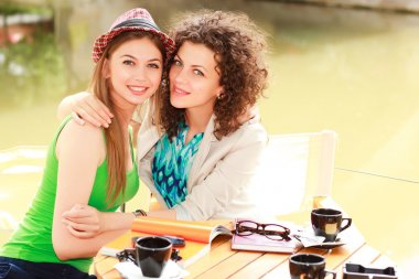 Two beautiful women drinking coffee and smiling on the river side terrace