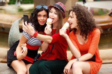 three beautiful women photographing themselves eating icecream