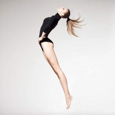 beautiful woman with perfect slim body and long legs jumping - fitness concept