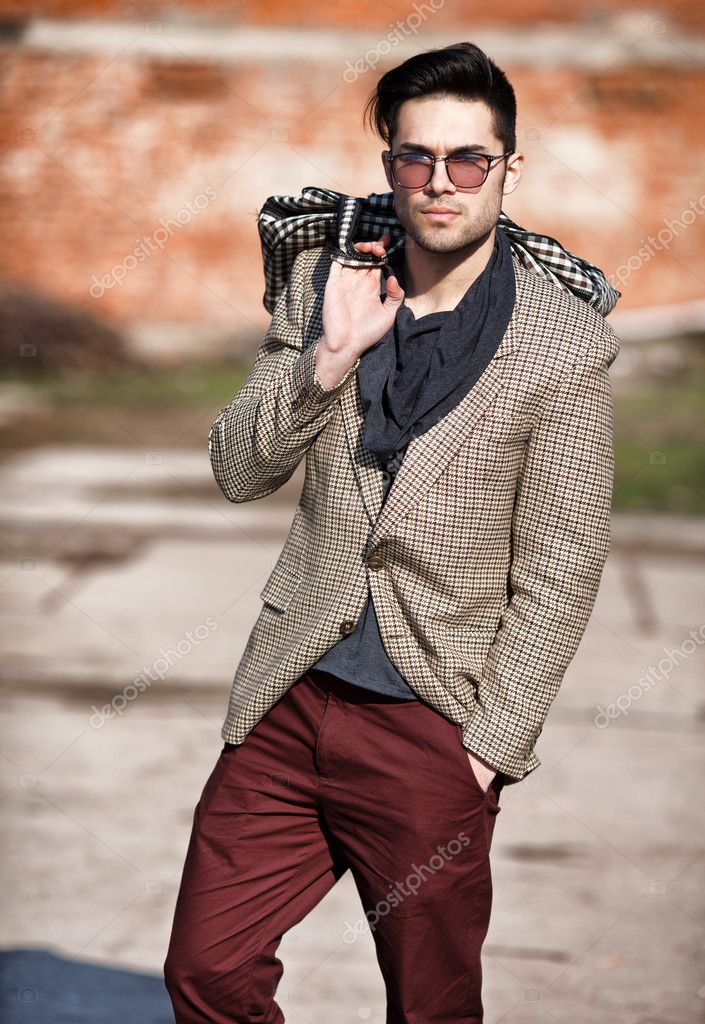 sexy fashion man model dressed elegant holding a bag posing outd