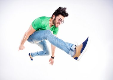 handsome man dressed casual jumping and smiling - dynamic wide
