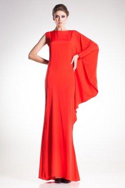 Beautiful woman model posing in simple elegant red dress in the studio