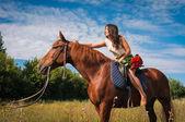 Fotografie Schöne Mädchen auf einem Pferd gegen blauen Himmel