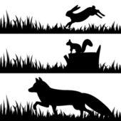 Silhouetten von Tieren im Gras.