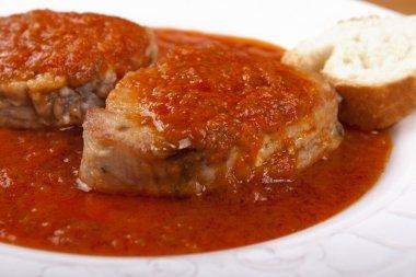 Tuna fish in tomato sauce and a slice of bread.