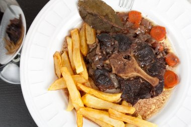 Oxtail stew with carrots and fries