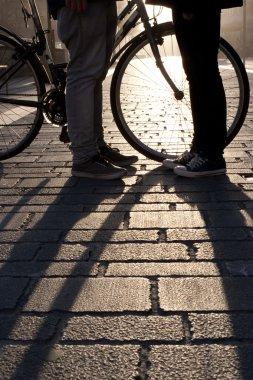 Legs of a young couple face to face with bicycle